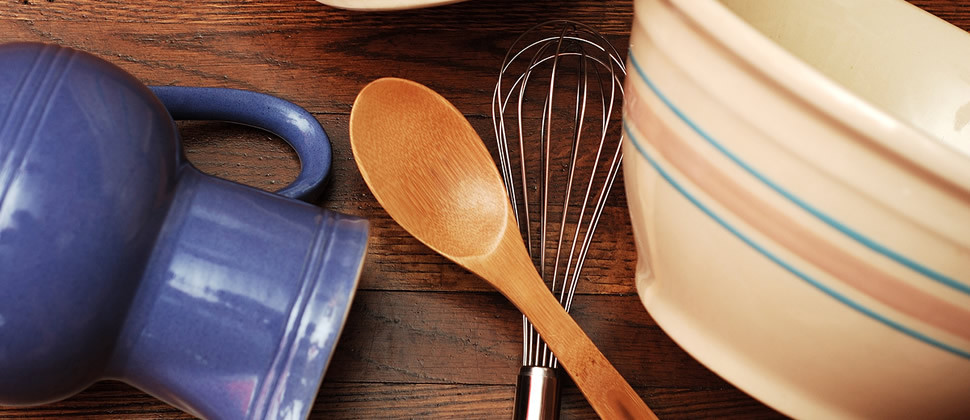 Close up of hardwood table and kitchen spoon, wisk, bowl and pitcher.