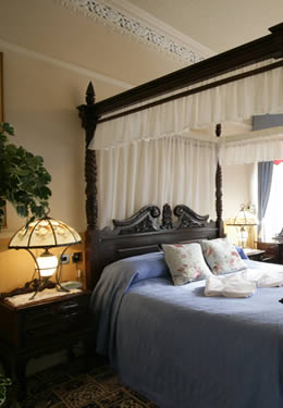 Victorian bed with blue linens and glowing light on the nightstand.