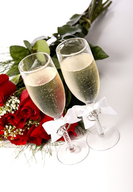 Two full champagne flutes tied with ribbons next to a boquet of a dozen red roses.