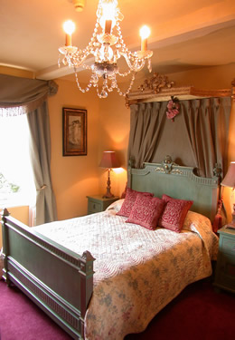 Tailored bed with antique furnishings and delicate chandelier.