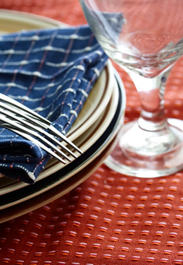 Stack of plates with two forks and a folded blue plaid napkin.