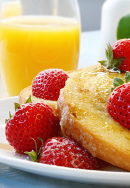 Bright breakfast plate with fresh strawberries, french toast and a full glass of orange juice.